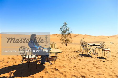 Man Sitting on Chair at Table in Desert, Erg Chebbi, Morocco Stock Photo - Rights-Managed, Image code: 700-03958220