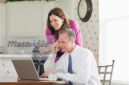 Couple Using Laptop and Drinking Coffee