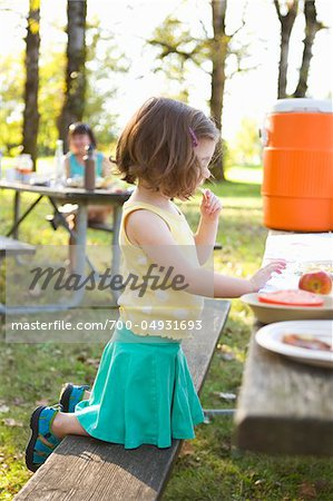 Little Girl Eating at Picnic Stock Photo - Rights-Managed, Image code: 700-04931693