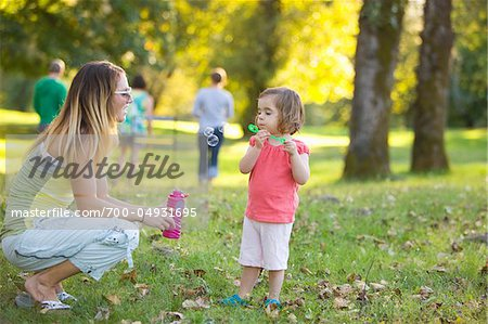 Little Girl and Woman Blowing Bubbles in Park Stock Photo - Rights-Managed, Image code: 700-04931695
