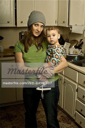 Mother Holding Son in Messy Kitchen Stock Photo - Rights-Managed, Image code: 700-04981807