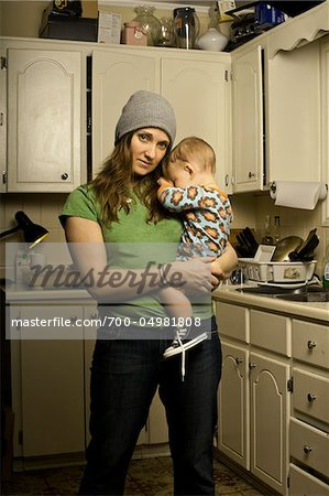 Mother Holding Son in Cluttered Kitchen Stock Photo - Rights-Managed, Image code: 700-04981808