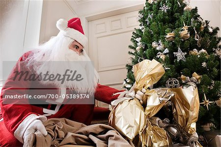 Man Dressed as Santa Claus Placing Gifts Underneath Tree