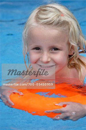 Girl Swimming with Orange Float in Swimming Pool Stock Photo - Rights-Managed, Image code: 700-05450959