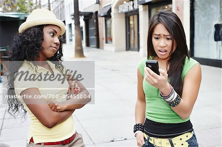 Woman with Cell Phone Looking Surprised While Friend Looks on Disapprovingly Stock Photo - Rights-Managed, Image code: 700-05451004