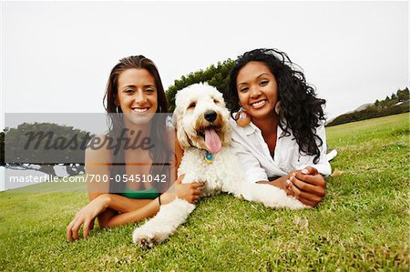 Two Women Lying on Ground with Dog Stock Photo - Rights-Managed, Image code: 700-05451042