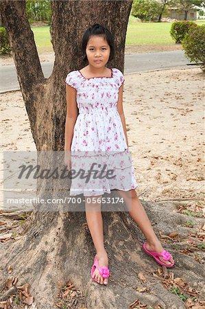 Girl Leaning Against Tree, Bangkok, Thailand Stock Photo - Premium ...