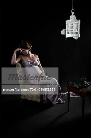 Pregnant Woman Sitting on Chair in Room with Birdcage and Telephone Stock Photo - Rights-Managed, Image code: 700-05653229