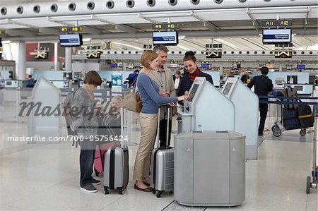Employee Helping Family Check In at Airport Stock Photo - Rights-Managed, Image code: 700-05756424