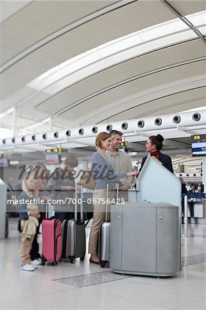 Employee Helping Family Check In at Airport Stock Photo - Rights-Managed, Image code: 700-05756425
