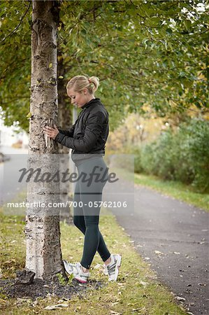Jogger Stretching Calves Against Tree Stock Photo - Rights-Managed, Image code: 700-05762106