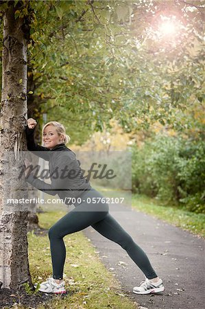Jogger Stretching Against Tree Stock Photo - Rights-Managed, Image code: 700-05762107