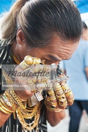 Man Wearing Lots of Jewelry Looking at Amulet Through Loupe Stock Photo - Rights-Managed, Image code: 700-05762115