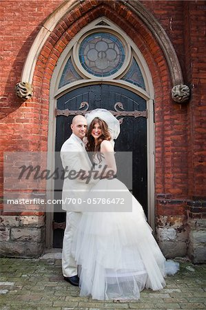Bride and Groom Standing in front of Church