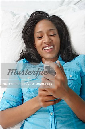 Woman Using Phone in Bed Stock Photo - Rights-Managed, Image code: 700-05803559