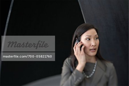 Businesswoman Talking on Cell Phone in Airport Terminal Stock Photo - Rights-Managed, Image code: 700-05821760