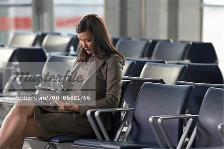 Businesswoman Using Tablet Computer in Airport Stock Photo - Rights-Managed, Image code: 700-05821766