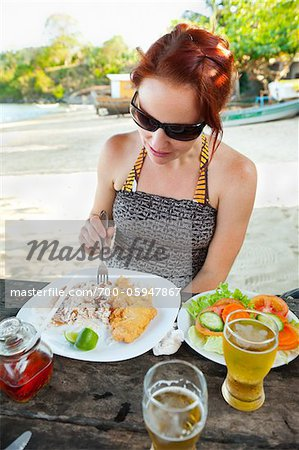 Woman Eating Meal of Fried Fish, Rice and Beans, and Salad at Beachside Cafe, near Paraty, Rio de Janeiro, Brazil Stock Photo - Rights-Managed, Image code: 700-05947867