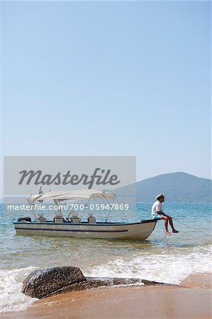 Man Sitting on Boat, near Paraty, Rio de Janeiro, Brazil Stock Photo - Rights-Managed, Image code: 700-05947869