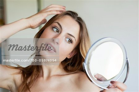 Woman Looking at Self in Mirror Stock Photo - Rights-Managed, Image code: 700-05974054