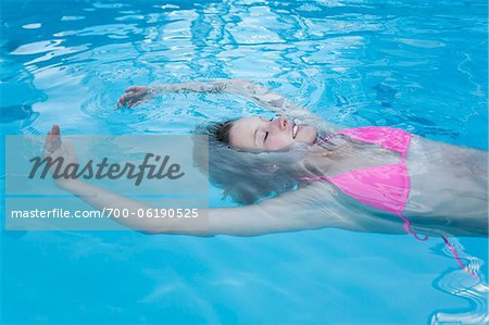 Teenage Girl Floating in Swimming Pool Stock Photo - Rights-Managed, Image code: 700-06190525