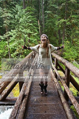 Young Woman with Open Arms Crossing Bridge Stock Photo - Rights-Managed, Image code: 700-06190624