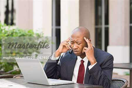 Stressed Businessman with Laptop and Cell Phone Stock Photo - Rights-Managed, Image code: 700-06282143