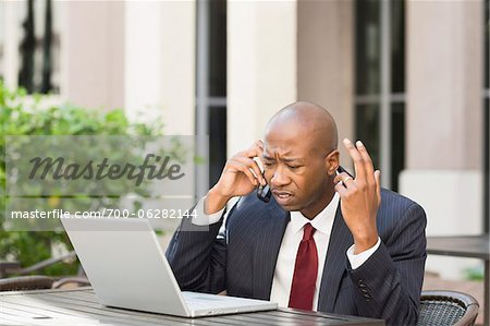 Stressed Businessman with Laptop and Cell Phone Stock Photo - Rights-Managed, Image code: 700-06282144