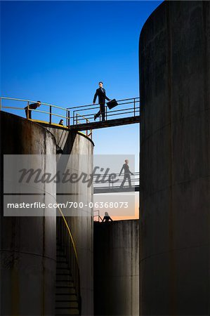 Businesspeople Walking Across Catwalks Between Storage Tanks Stock Photo - Rights-Managed, Image code: 700-06368073