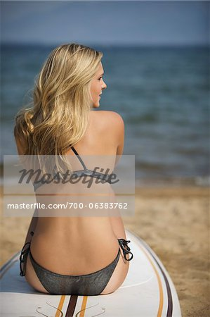 Young Woman Sitting on Surfboard