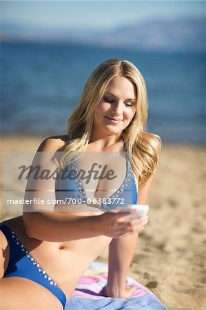 Young Woman with Cell Phone on Beach Stock Photo - Rights-Managed, Image code: 700-06383772