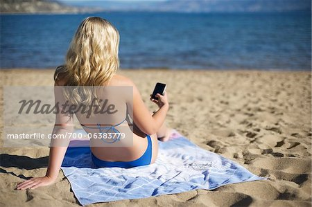 Rear View of Woman on Beach with Cell Phone Stock Photo - Rights-Managed, Image code: 700-06383779