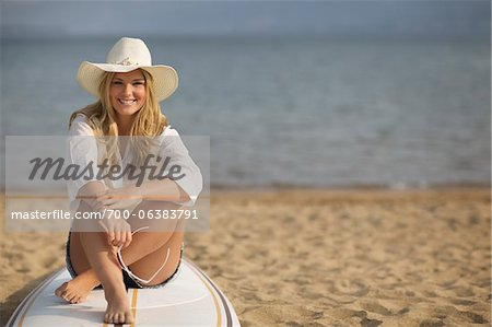 Portrait of Woman Sitting on Surfboard Stock Photo - Rights-Managed, Image code: 700-06383791