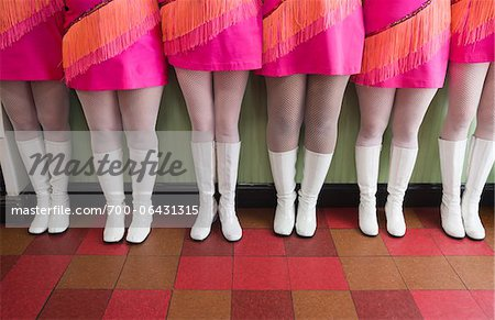 Waist Down View of Six Women Dressed in Vintage Pink Dresses and White Go-go Boots Standing in a Row on Checkered Floor Stock Photo - Rights-Managed, Image code: 700-06431315