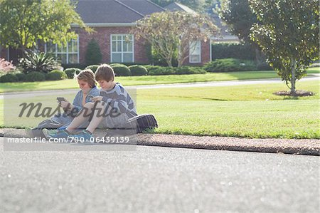 Two Boys Sitting on Neighbourhood Curb with Handheld Electronics Stock Photo - Rights-Managed, Image code: 700-06439139