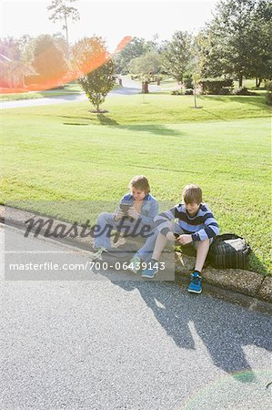 Two Boys Sitting on Neighbourhood Curb with Handheld Electronics Stock Photo - Rights-Managed, Image code: 700-06439143