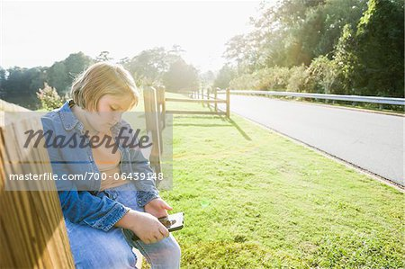 Boy Sitting Outdoors on Roadside Fence with Tablet Computer Stock Photo - Rights-Managed, Image code: 700-06439148