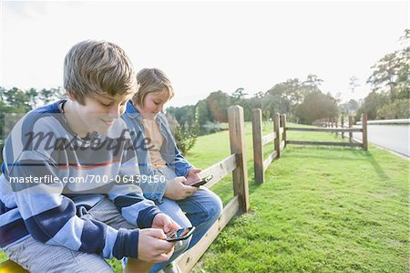 Two Boys with Handheld Electronics Sitting on Roadside Fence Stock Photo - Rights-Managed, Image code: 700-06439150