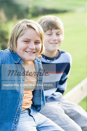 Portrait of Two Boys Sitting Outdoors on Fence Stock Photo - Rights-Managed, Image code: 700-06439151
