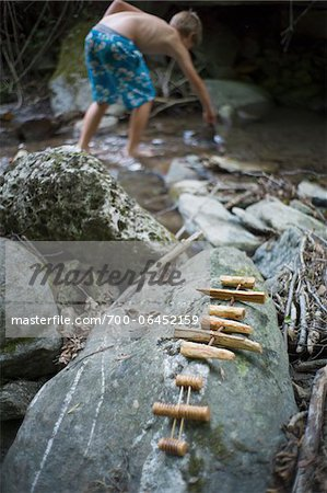 Small Boats Made with Wood on Rock by River with Boy in Background Stock Photo - Rights-Managed, Image code: 700-06452159