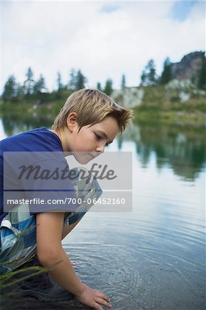 Boy Crouching by Lakeshore with Hands in Water Stock Photo - Rights-Managed, Image code: 700-06452160