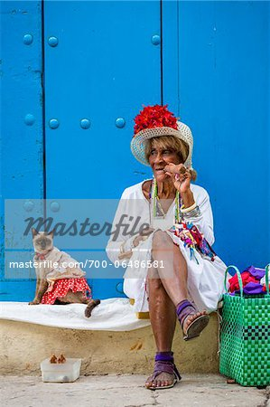 Woman Smoking Cigar and Sitting on Curb with Cat Wearing Costume, Old Havana, Havana, Cuba Stock Photo - Rights-Managed, Image code: 700-06486581