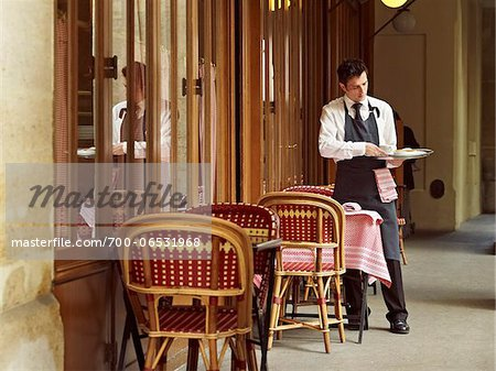 waiter clearing dishes at charming outdoor cafe, Fontaine de Mars, Paris, France Stock Photo - Rights-Managed, Image code: 700-06531968