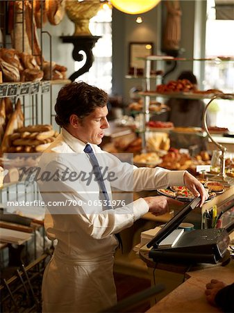 Waiter in Wearing Shirt, Tie, and Apron Operating Cash Machine in Bakery, Paris, France Stock Photo - Rights-Managed, Image code: 700-06531976