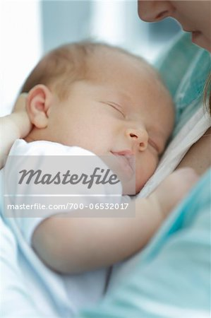 newborn baby girl in a white undershirt sleeping in the arms of mother wearing a blue shirt Stock Photo - Rights-Managed, Image code: 700-06532017