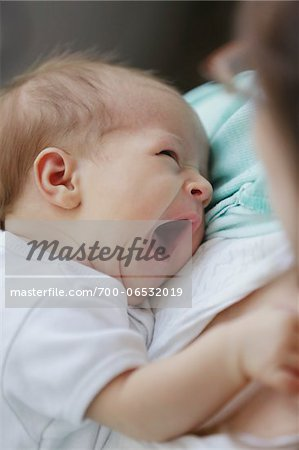 newborn baby girl in a white undershirt yawning in the arms of her mother Stock Photo - Rights-Managed, Image code: 700-06532019