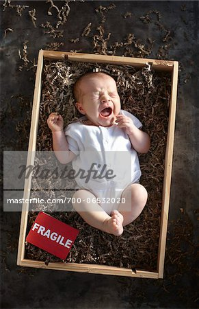yawning newborn baby girl wearing white undershirt onesie in a shipping box labeled as fragile with packing paper Stock Photo - Rights-Managed, Image code: 700-06532020