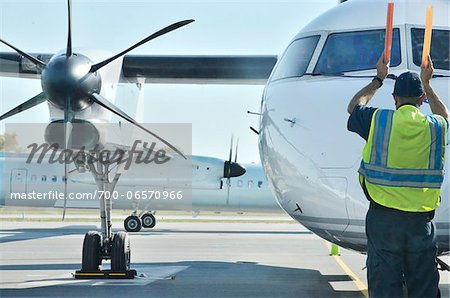 airport ramp marshall signalling plane in for arrival Stock Photo - Rights-Managed, Image code: 700-06570966