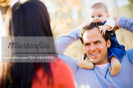 Man Carrying Four Month Old Daughter on his Shoulders while Talking with Woman, Outdoors at Scanlon Creek Conservation Area, near Bradford, Ontario, Canada Stock Photo - Rights-Managed, Image code: 700-06674976