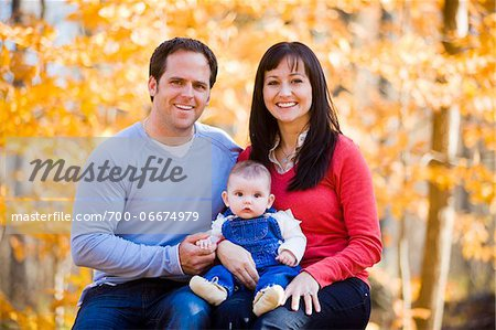 Portrait of Couple Sitting and Holding their Four Month Old Daughter, at Scanlon Creek Conservation Area, near Bradford, Ontario, Canada Stock Photo - Rights-Managed, Image code: 700-06674979